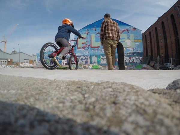A child on their bike and a skateboarder at a skatepark