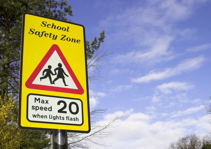A school saftey zone road sign with a 20mph speed limit notice